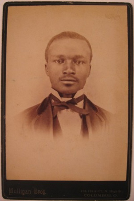 Upper body portrait of a Black man in suit with wing collar and bow tie.