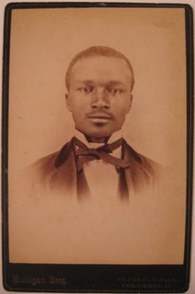 Upper body portrait of a Black man in suit with wing collar and bow tie